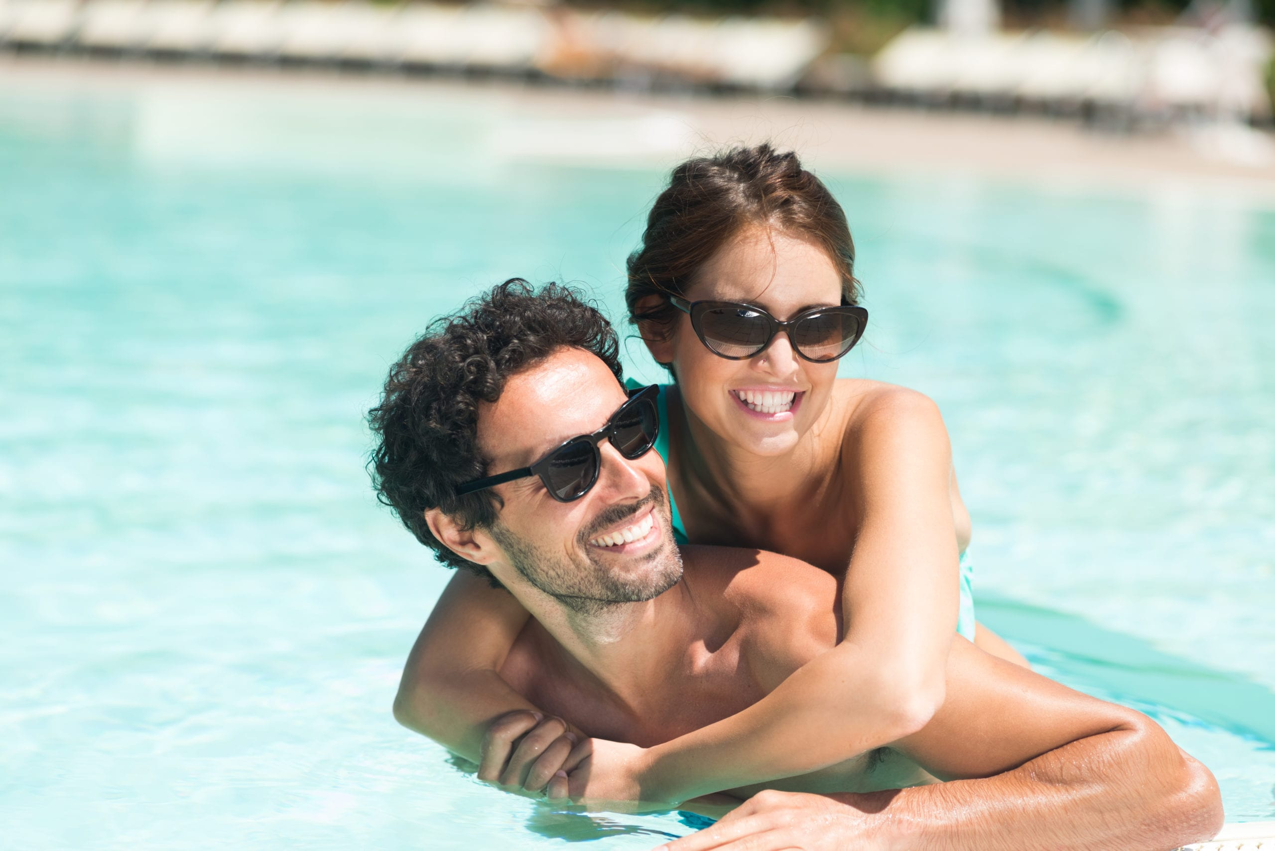 couple swimming together in sunny pool amenities at san francisco apartment